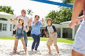 Grandparents And Grandchildren Playing Volleyball In Garden