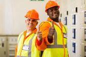 cheerful electrical engineers giving thumbs up