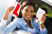 happy african female driver tearing up her L sign sitting in a car