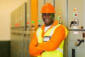 professional african industrial technician in front of control panel