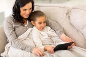 beautiful daughter using tablet computer with her mother on sofa