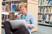 Male College Student Studying In Library With Laptop