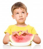 Cute little boy is eating watermelon, isolated over white