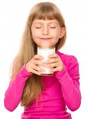 Happy little girl with a glass of milk, isolated over white