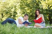 Portrait Of Happy Couple Reading Book In Park