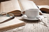 picture of french culture  - cup of coffee on rustic wooden table with open books - JPG