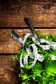 Fresh Salad With Fitness Measuring Tape On Wooden Background With Knife And Fork Close Up. Diet Food