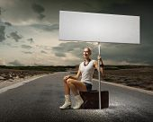 Young woman with blank banner sitting on suitcase
