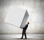 Young businessman carrying white big cube. Place for text