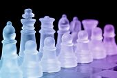 Chess pieces on check board with selective focus on king