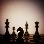 Chess pieces in silhouette on board with spotlight in background