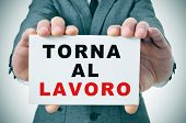 businessman holding a signboard with the text torna al lavoro, back to work in italian, written in i