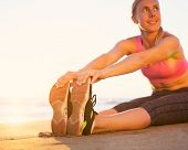 Athletic fitness woman stretching her legs on the beach at sunset