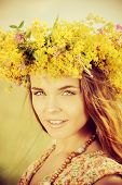 Romantic girl in a wreath of wild flowers standing in a field. Summer life.
