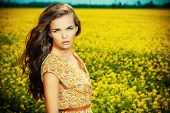 Beautiful girl standing in a field of blooming yellow flowers. Summer.