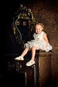 Cute little girl in a beautiful white dress sitting on the fireplace in the room. Vintage style.