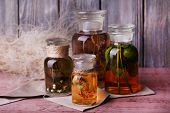 Bottles of herbal tincture on a napkin on  wooden table in front of wooden wall