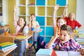 Clever schoolkids raising hands at workplaces during lesson