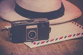 Nostalgic travel explorer concept photo, old film camera, hat and airmail letter on canvas