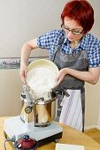 foto of food processor  - Woman pour wheat flour into food processor while baking - JPG