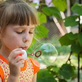 Beautiful girl blows a big bubble