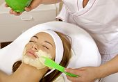 young woman getting beauty skin mask treatment on her face with brush