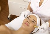 Young brunette woman receiving laser therapy. Spa studio shot