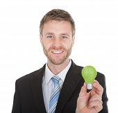 Businessman Holding Green Light Bulb