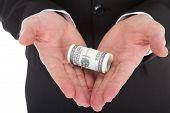 Businessman's Hands Holding Tied Dollar Bills