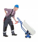 Worker Suffering From Backache While Pushing Machinery