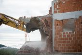 image of backhoe  - View of the hydraulic arm and bucket of a large heavy duty backhoe demolishing a brick house breaking down the exterior wall for removal - JPG