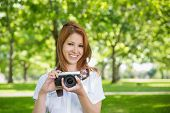 Pretty redhead holding her camera in the park on a sunny day
