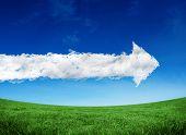 Cloud arrow against green field under blue sky