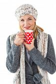 Smiling woman in winter fashion looking at camera with mug on white background