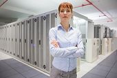 Serious data technician looking at camera in large data center