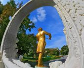 VIENNA, AUSTRIA - SEPTEMBER 27, 2013: Elegant gilded statue of Johann Strauss, playing the violin in white marble arch. Park in Vienna