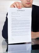 Businessman Showing Contract Paper At Desk