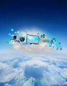 Laptop on floating cloud with apps against blue sky over clouds at high altitude
