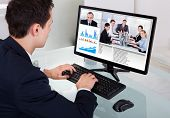 Businessman Video Conferencing With Team In Office