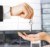 real estate concept - picture of man hand passing house keys to woman