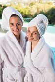 Portrait of two smiling young women in bathrobes