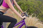 Close up side view of an athletic young woman mountain biking