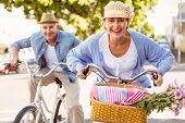 Happy mature couple going for a bike ride in the city on a sunny day