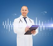 medicine, profession, cardiology and healthcare concept - smiling male doctor with clipboard and ste