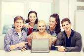 education, technology, advertisement and internet concept - group of smiling students pointing to bl