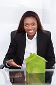 Businesswoman Showing Green Colored House At Desk