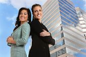 Two businesswomen with arms crossed with office building in background