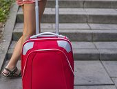 Girl's legs on the steps outdoors with a red suitcase, travel concept.