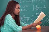 African American Teacher Reading Book At Classroom Desk