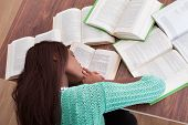 Female Student Sleeping With Books At Classroom Desk